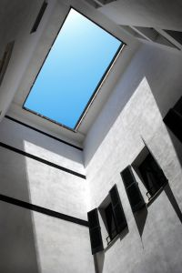 Window in the roof, revealing a striking square of blue sky